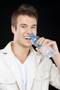 Handsome man drinks water from Royalty Free Stock Photos