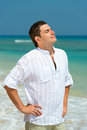 Handsome man enjoy vacation on a beach with blue sea background Stock Photo