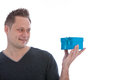 Handsome man eyeing a blue gift box balanced on his hand as he tries to guess what is inside on his birthday or christmas isolated Royalty Free Stock Photography