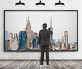 A handsome man in formal clothes is drawing a picture of New York City. Wooden floor, concrete wall and three black ceiling lights Royalty Free Stock Photo