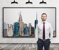 A handsome man in formal clothes stands in front of the picture of New York City on the wall. Royalty Free Stock Photo