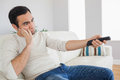 Handsome man getting bored of tv programs on cosy sofa Stock Images