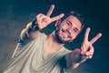 Handsome man guy giving peace v sign gesture portrait of happy smiling victory in studio on black Stock Images