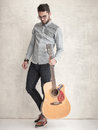 Handsome man holding an acoustic guitar against grunge wall Royalty Free Stock Photo