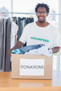 Handsome man holding a donation box full of clothes Royalty Free Stock Photography