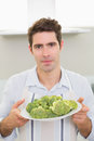 Handsome man holding a plate of broccoli in kitchen portrait smiling young Stock Image