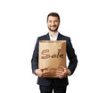 Handsome man holding shopping bag smiley in formal wear with sale written on them isolated on white background Stock Photos