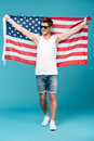 Handsome man holding USA flag. Looking aside. Royalty Free Stock Photo