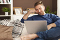 Handsome man at home smiling relaxing with laptop Royalty Free Stock Images