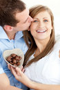 Handsome man kissing girlfriend holding chocolate Royalty Free Stock Photos