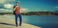 Handsome man by lake panoramic view of a walking the side of a blue in summer Stock Image