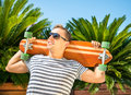 Handsome man leaning against green palms and holding his long board Royalty Free Stock Photo