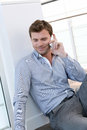 Handsome man making a phonecall sitting on the floor Royalty Free Stock Photo
