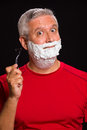 Handsome man middle age with shave cream on a black background Royalty Free Stock Photo