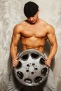 Handsome man with muscular torso sporty body holding alloy wheel Stock Photo