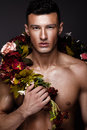 A handsome man with a naked torso, bronze tan and flowers on his body.