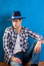 Handsome man with plaid shirt and cowboy hat Stock Photos