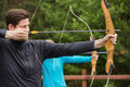 Handsome man practicing archery men at the range Royalty Free Stock Photography