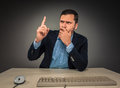 Handsome man raised his index finger and looking at camera the sitting a desk near a computer isolated on gray background Royalty Free Stock Photography