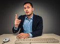 Handsome man raised his index finger and looking at camera the sitting a desk near a computer isolated on gray background Stock Photo