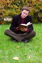Handsome man reading book on a grass in autumn Stock Image