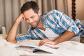 Handsome man relaxing on his bed reading magazine Royalty Free Stock Photo