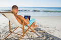 Handsome man scrolling on his tablet pc the beach Royalty Free Stock Photo