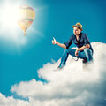 Handsome man with a sign hitch hiking young traveller sitting on clouds Royalty Free Stock Image