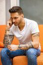 Handsome man sitting on couch talking on phone Royalty Free Stock Photo