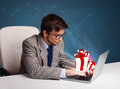 Handsome man sitting at desk and typing on laptop with present b young boxes icons Royalty Free Stock Photos