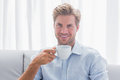 Handsome man sitting on his couch drinking a coffee in the living room Royalty Free Stock Photo