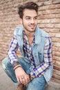 Handsome man sitting near a brick wall Royalty Free Stock Photo