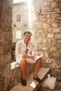 Handsome man sitting on old street and holding map in hands Royalty Free Stock Photo