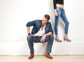 image photo : Handsome man sitting with a pair of female legs in background