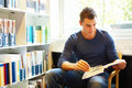 Handsome man sitting and reading in library Stock Photo