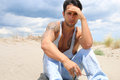 Handsome man sitting on the sand Royalty Free Stock Photo