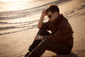 Handsome man sitting and thinking on sand dune Royalty Free Stock Photo