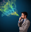 Handsome man smoking cigarette with colorful smoke