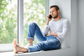 Handsome man speaking on mobile phone sitting on window sill Royalty Free Stock Photo