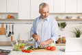 Handsome man standing at the kitchen using laptop and cooking Royalty Free Stock Photo