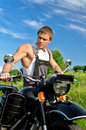 Handsome man standing near motorcycle. Royalty Free Stock Photos