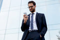 Handsome man in a stylish suit reads a message from a favorite stand next to the office building Royalty Free Stock Photo