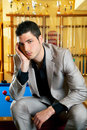 Handsome man with suit sitting in billiard pool Royalty Free Stock Photography