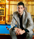 Handsome man with suit sitting in billiard pool Royalty Free Stock Images