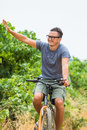 Handsome man in sun glasses is smiling while cycling in the park Royalty Free Stock Photo
