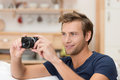 Handsome man taking a photograph young indoors lining up the camera composing the image and focusing Stock Images
