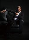 Handsome man in a tuxedo on couch Stock Photography