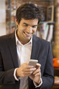 Handsome man using a cell phone in coffee bar male cheerful mobile smiling restaurant Royalty Free Stock Image