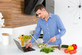 Handsome man using laptop and cooking on the kitchen Royalty Free Stock Photo