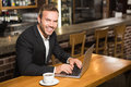 Handsome man using laptop and having a coffee in pub Stock Images